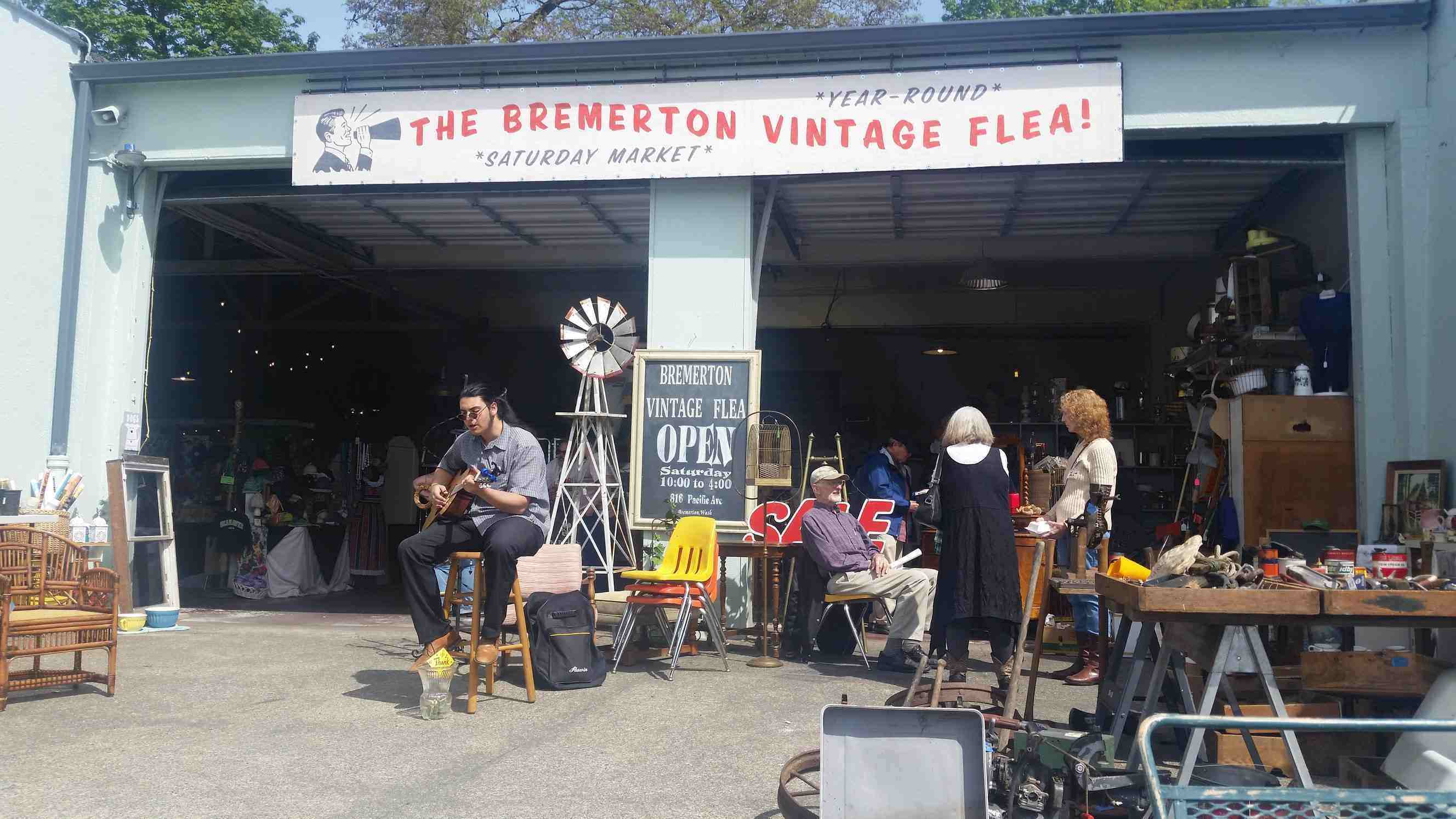 The bremerton flea market with a guy sitting infront playing guitar
