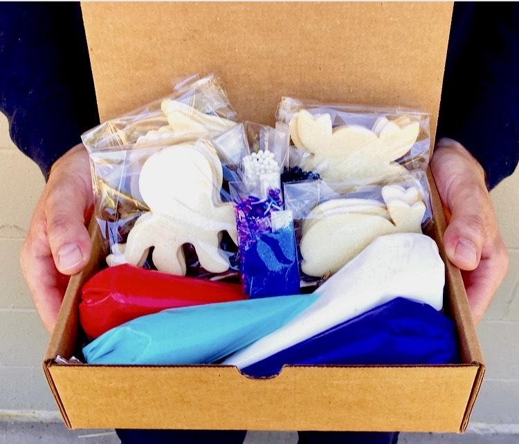 Hands holding box of undecorated cookies and tubes of frosting.