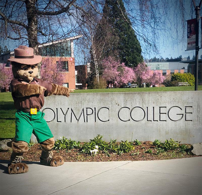Olympic College mascot in front of college sign