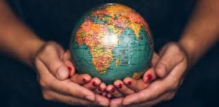 The world globe cradled by open hands