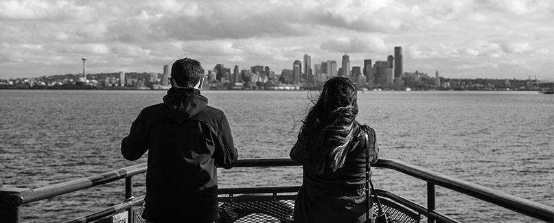 Black and white photo on a man and women on the ferry with Seattle in the background.