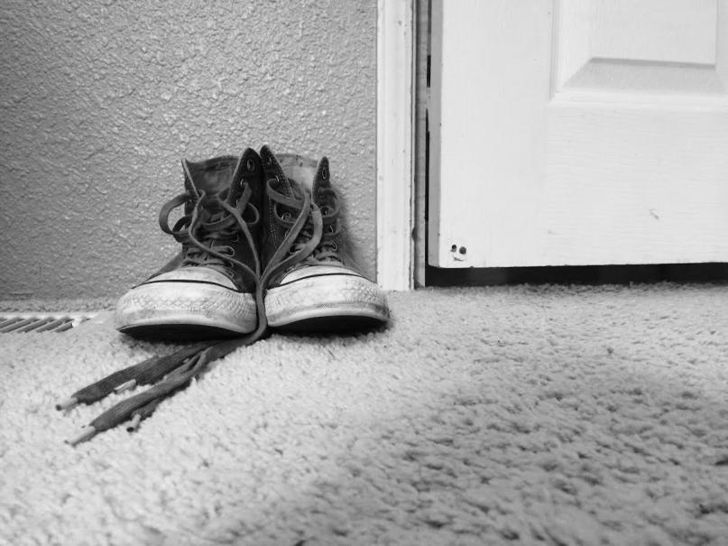 Black and white photo of a pair of sneakers on carpet next to a door