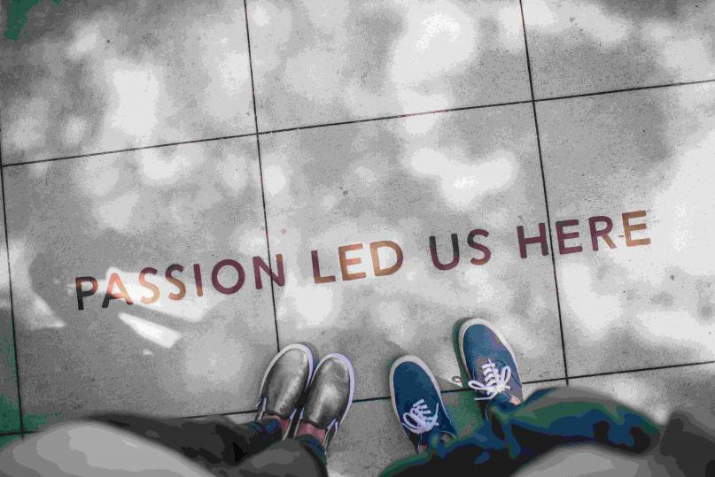 """Looking down at shoes on a sidewalk that says """"Passion Led Us Here"""""""