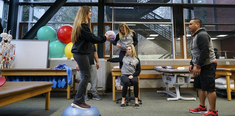 PTA students using therapy ball in lab