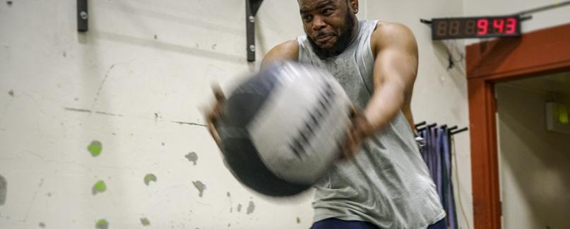 Student working out with medical ball.