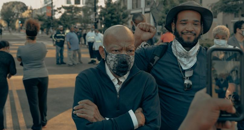 Elderly Black man in a cloth face mask by a young Black man raising his fist and smiling are photographed by a cell phone