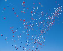 a scnery of multiple colors of helium balloons floating in the sky