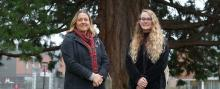 Amy Lawrence and Kelsey Alvarez posing in front of a tree on the Olympic College campus