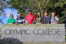 staffs from multicultural team standing behind a Olympic College logo