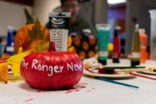 Pumpkin painted red with the ranger news written in white on it.