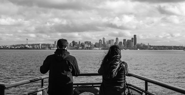 Two people looking out over the water with the Seattle skyline off in the distance